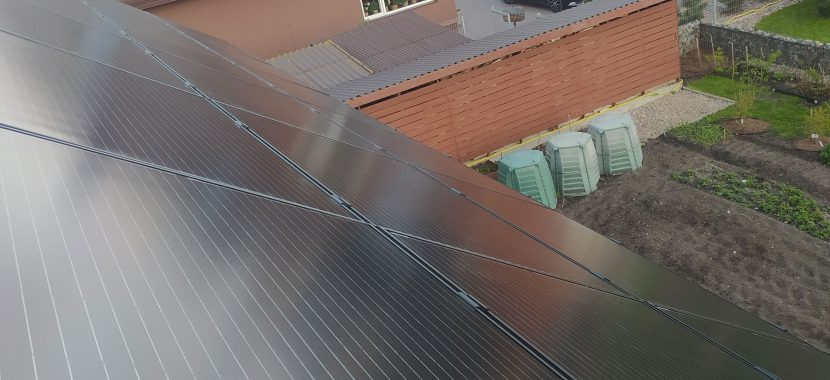 saulės elektrinė su juodais fotovoltiniais moduliais ant nuožulnios stogo dangos